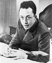 200px-Albert_Camus,_gagnant_de_prix_Nobel,_portrait_en_buste,_posé_au_bureau,_faisant_face_à_gauche,_cigarette_de_tabagisme